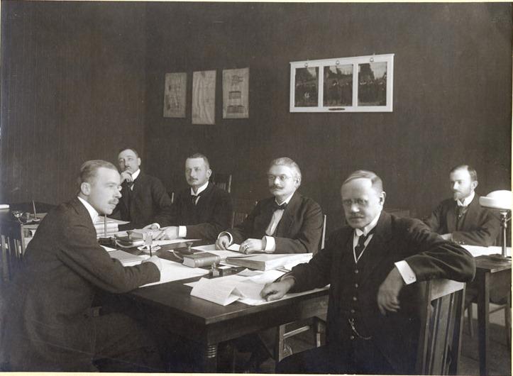 svartvit bild på Åbo Akademis konsistorium, sex män vid ett mötesbord