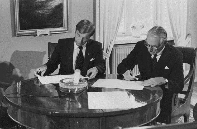 Två män vid ett bord undertecknar avtal.