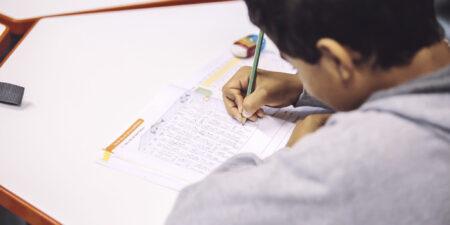 Skolelev, klassrum, skriver en uppgift