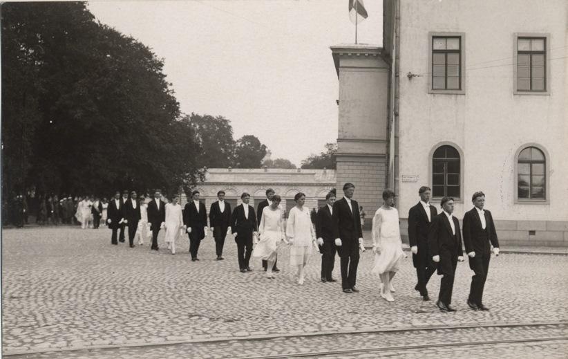 Åbo Akademis första promotion 1927. Promovender gående i procession över domkyrkotorget. I bakgrunden gamla akademihuset och landshövdingens magasin.