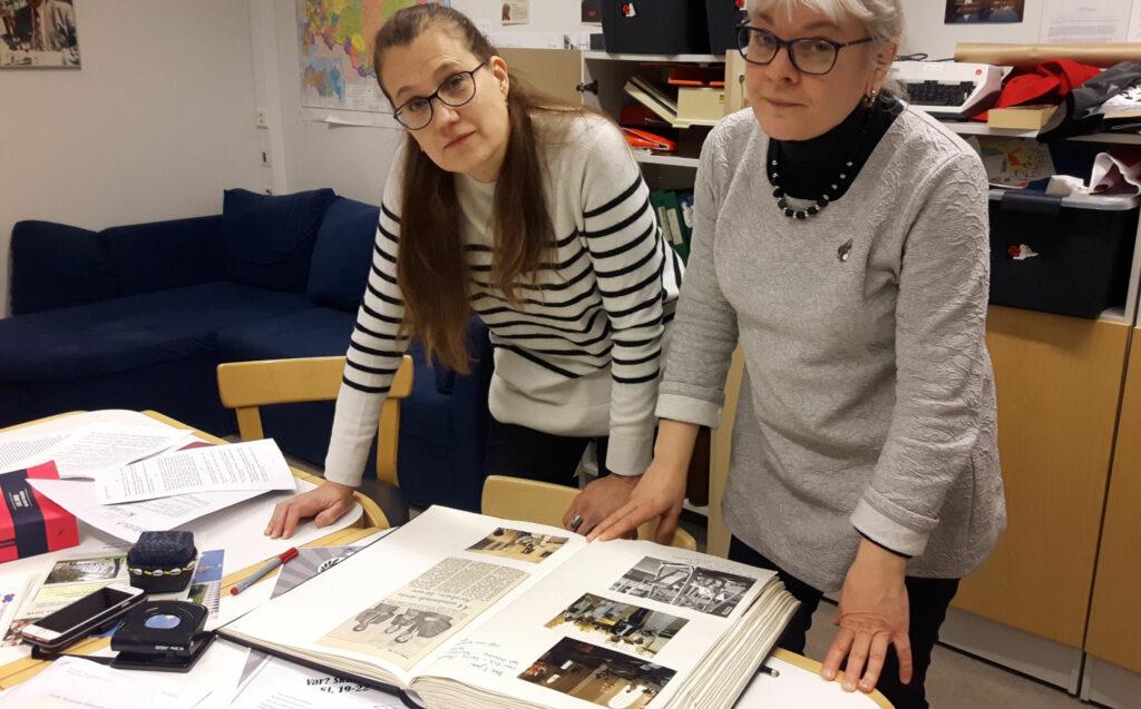 Martina Björklund och Anna-Stina Nyby bläddrar i urklippsböcker