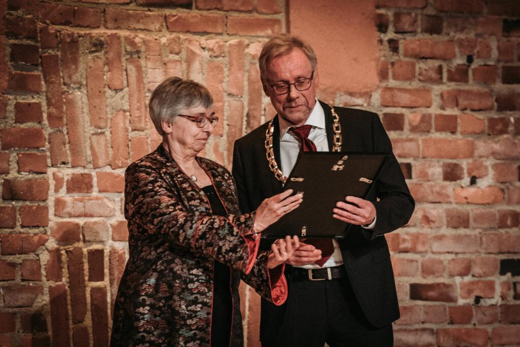 En kvinna och en man håller i en tavla