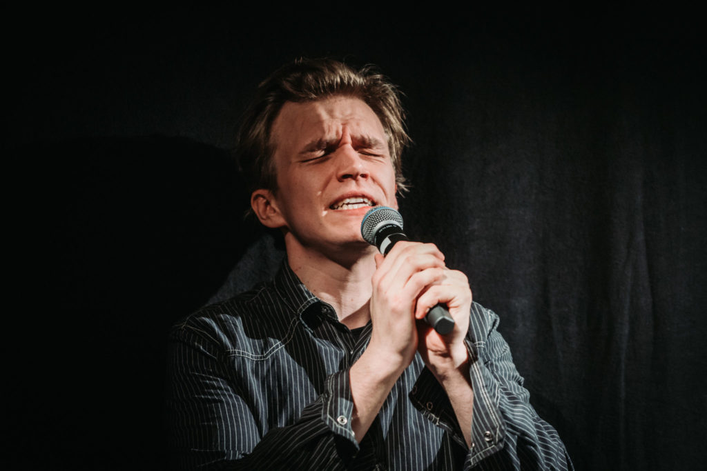 En ung man sjunger i mikrofon