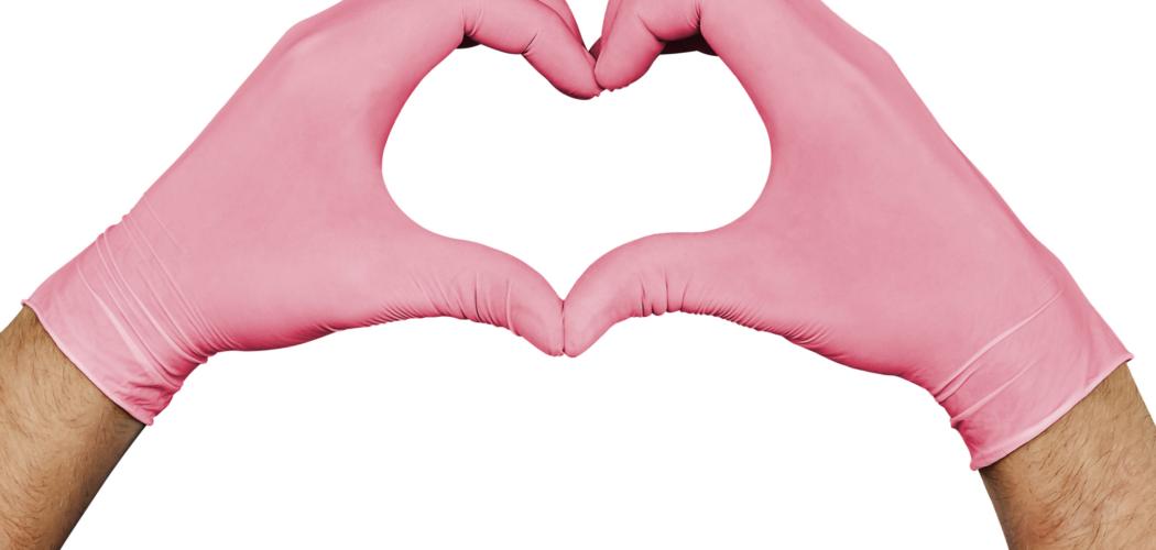 Händer iklädda rosa gummihandskar formar ett hjärta. Vit bakgrund.