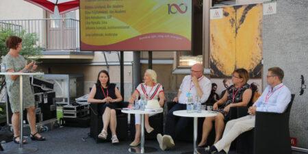 Personer sitter på rad i en paneldebatt