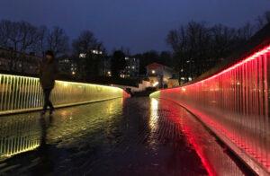 En bro fotograferad i mörker, upplyst i rött och gult.