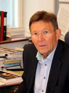 Porträttfoto på Tapio Westerlund framför sitt skrivbord.