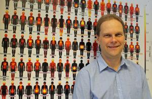 Lauri Nummenmaa framför affisch med människosihuetter som visar smärtställen i kroppen.