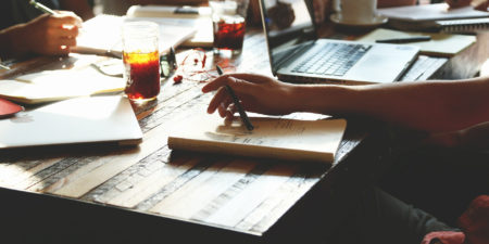 en hand villar mot ett papper ochhåller i en penna