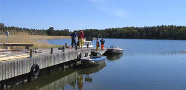 Husö biologiska stations brygga med tre båtar och fyra personer