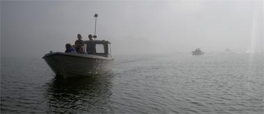 Kursister kommer åkande med båt i dimma