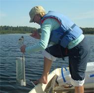 En person i båt tar vattenprov från havet med hjälp av en Limnos vattenhämtare