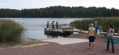 Strandvy med kursister på väg till båtar vid bryggan