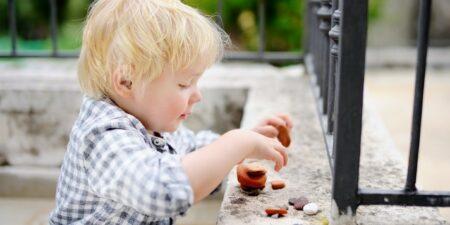 Barn leker med stenar på träbänk.
