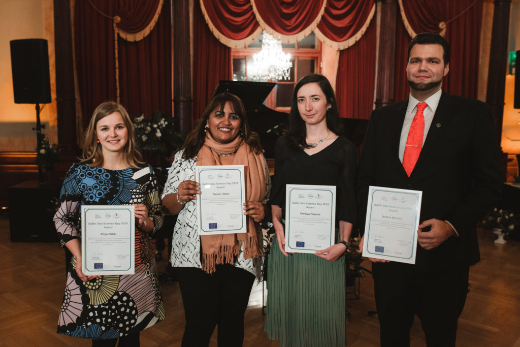 Four young award winners standing with diplomas in their hands.