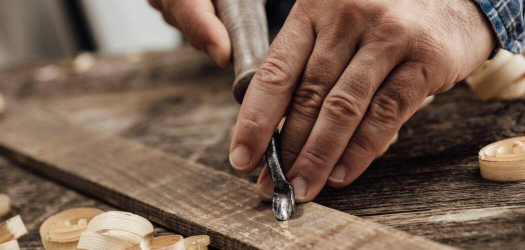 Bild på händer som slöjdar, karvar trä.