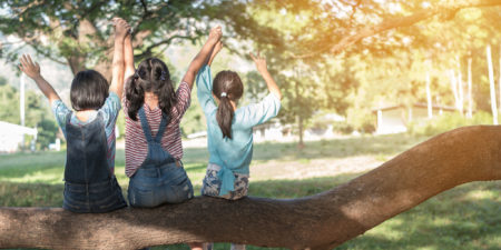 Bild på glada barn i en solig, somrig park.