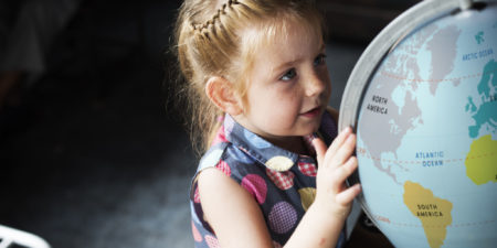 flicka som undersöker jordglob
