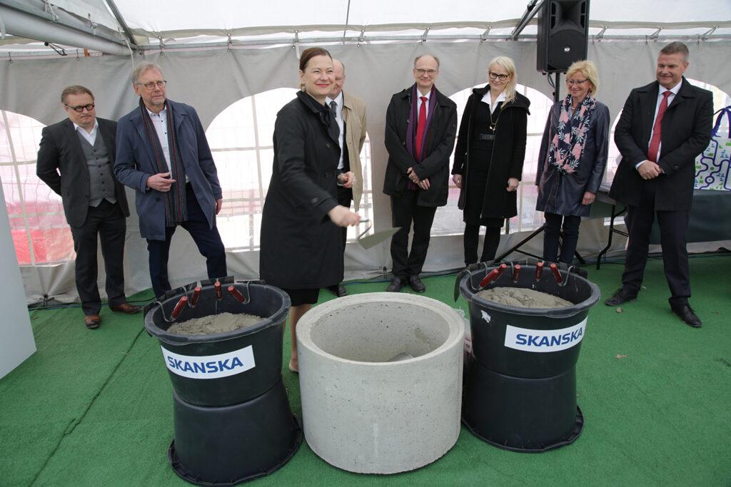 Stadsdirektör Minna Arve lägger en skopa murbruk i grundstenen.