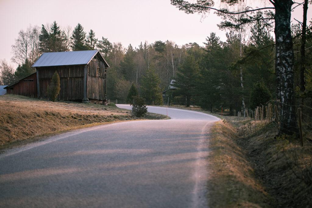 Asfalterad väg slingrar sig ut bakom en lada med skog i bakgrunden.