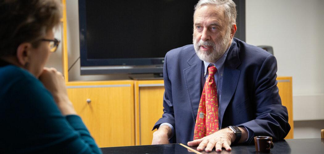 Foto på James Fishkin sittande vid ett bord, pratande med en journalist.