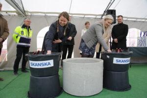 TYY:s ordförande Sini Saarinen och ÅAS:s ordförande Anna Oksanen skopar murbruk.