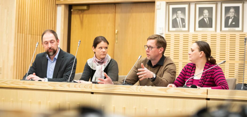 Fyra personer sitter bakom ett träfärgat podium och diskuterar under medborgarrådet i Korsholm. Svartvita porträtt i bakgrunden.