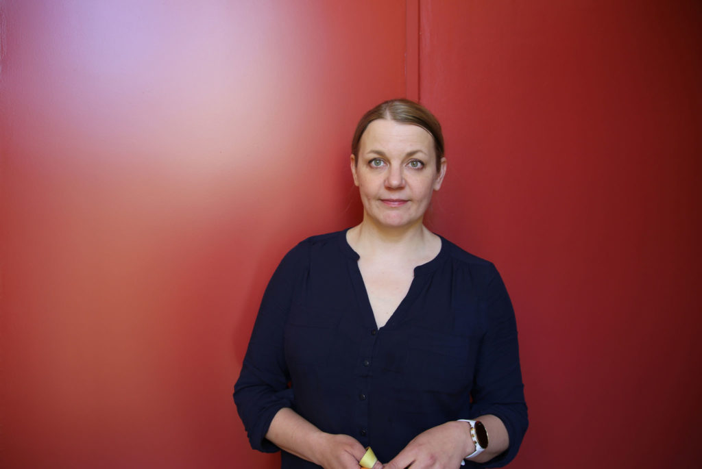 Researcher Nina Tynkkynen stands in front of a red wall.