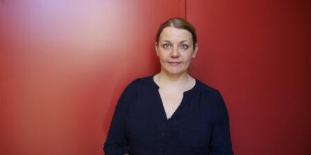 Forskare Nina Tynkkynen står framför en röd vägg.
