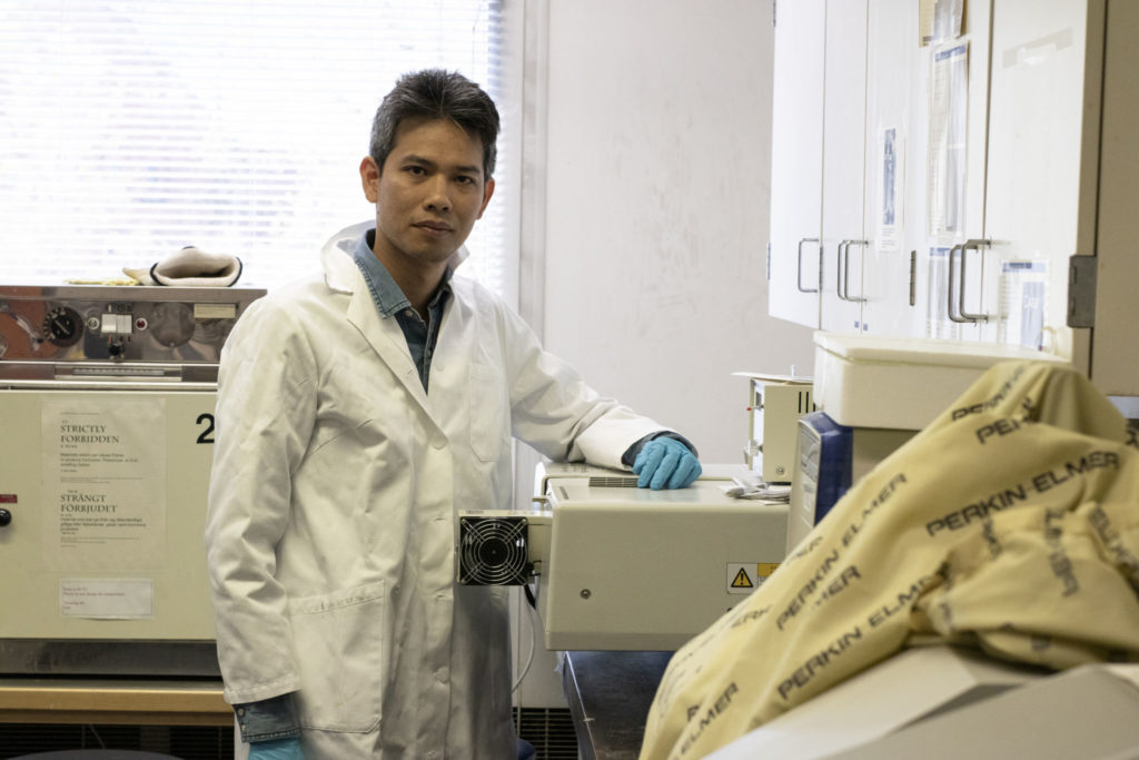 Tan Phat Huynh iförd laboratoriekläder i ett laboratorium.