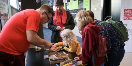 Besökare på Vetenskapsdagarna undersöker arkeologiska fynd.