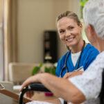 Vårdare tittar leende på en äldre patient.