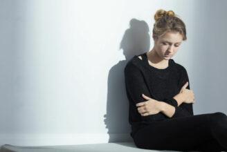 En ung kvinna som sitter mot en vägg och håller armarna om sig själv