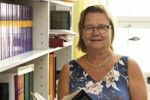 Malin Brännback står med en bok i handen framför en bokhylla.