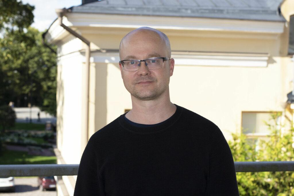 Porträttfoto på Tuomas Martikainen iförd svart collegetröja.