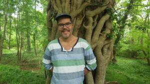 Oriol Poveda Guillén står lutad mot ett träd.