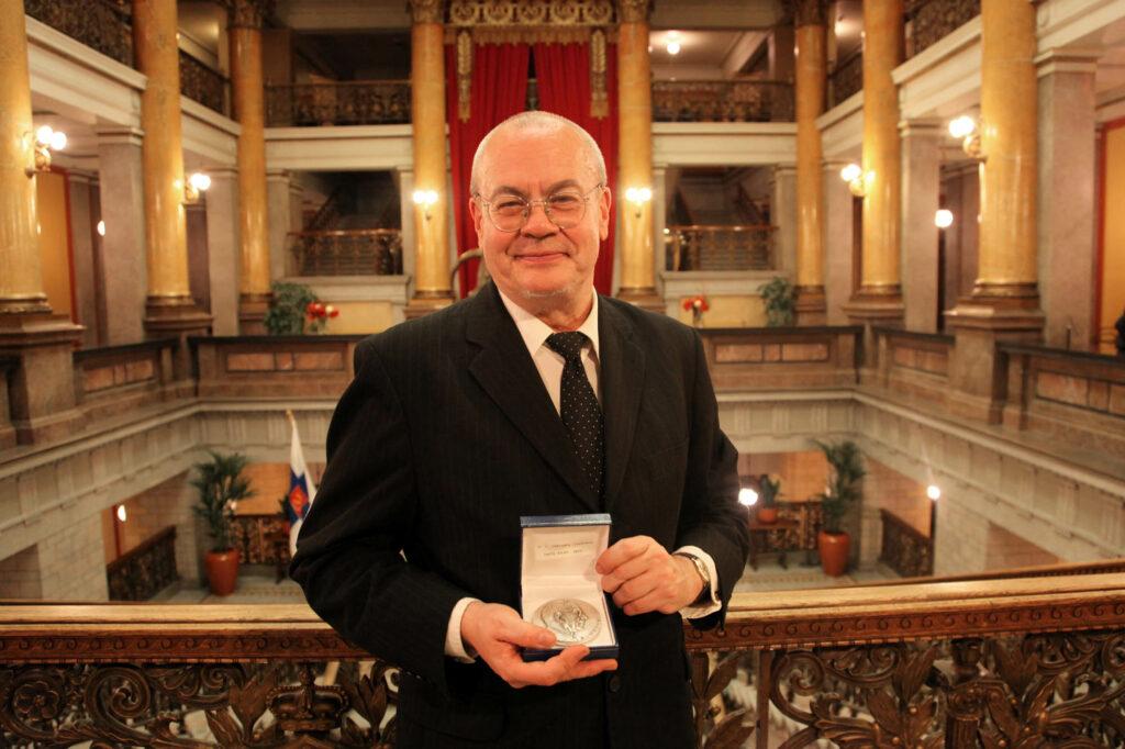 Kostymklädd Tapio Salmi med A. I. Virtanen-medaljen i händerna.