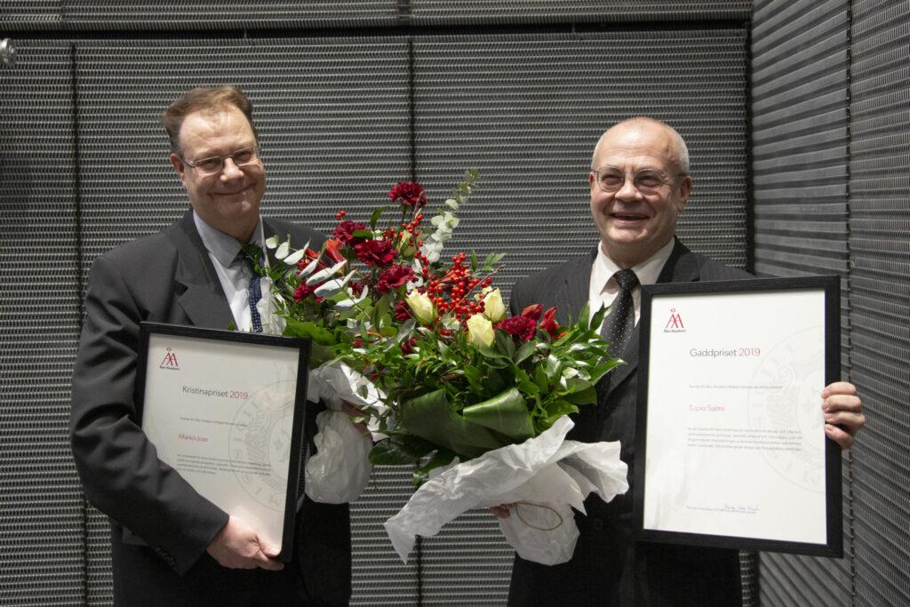 Marko Joas och Tapio Salmi står leende med buketter och plaketter i händerna.