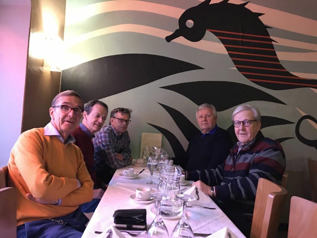 Fem män sitter vid ett bord och dricker kaffe.