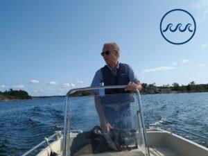 Erik Bonsdorff kör en båt. I bakgrunden synd blått hav och blå himmel.