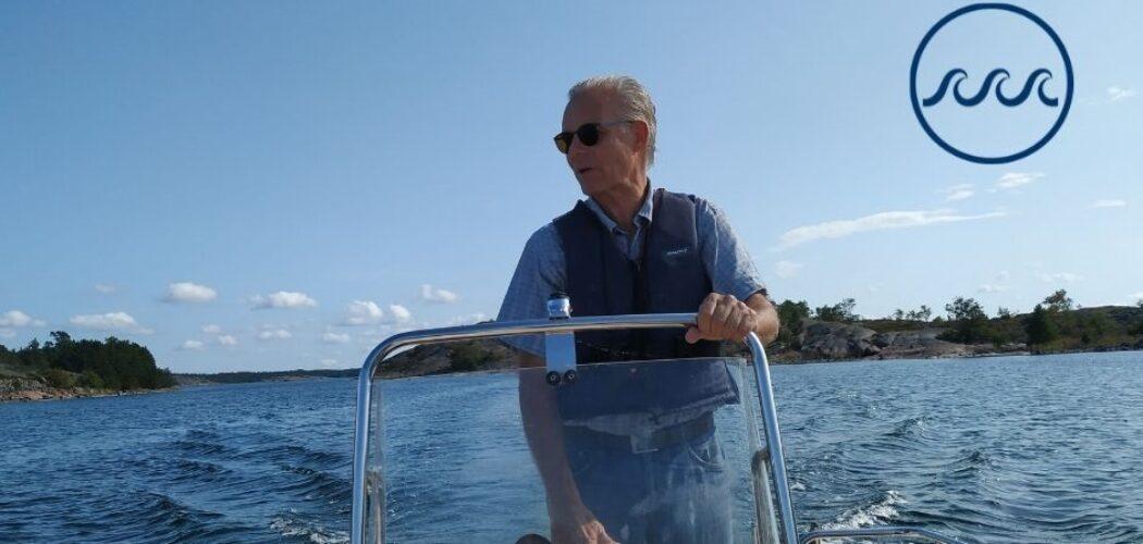Professor Erik Bonsdorff kör en båt stående. I bakgrunden blått hav och blå himmel och uppe i höger hörn logon för det strategiska profilområdet Havet. Logon består av en cirkel med tre vågor i mitten.