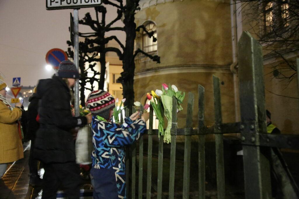Barn fäster blommor på staketet utanför synagogan i Åbo.