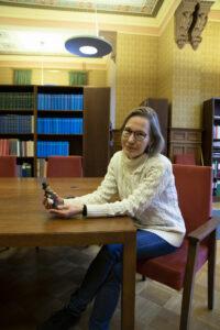 Ruth Illman sitter vid ett bord med en liten souvenir i handen.