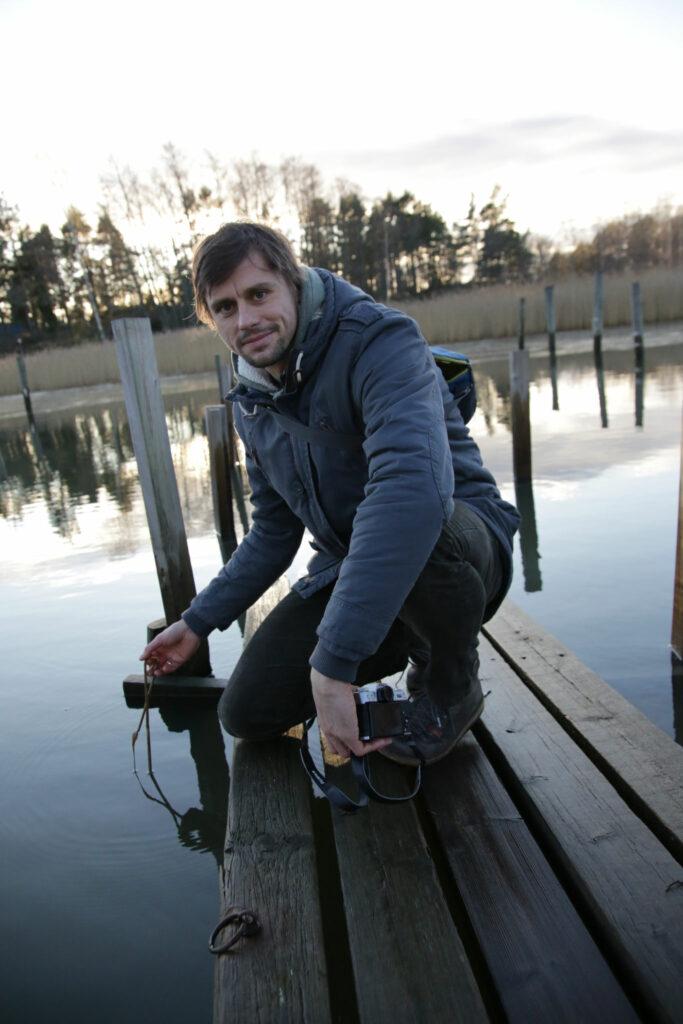 Christian Pansch hukad på knä på en brygga, håller vasstrå i handen.
