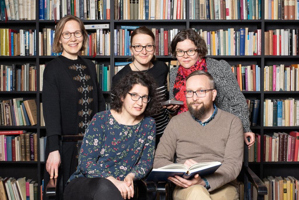 Forskargrupp framför bokhylla.