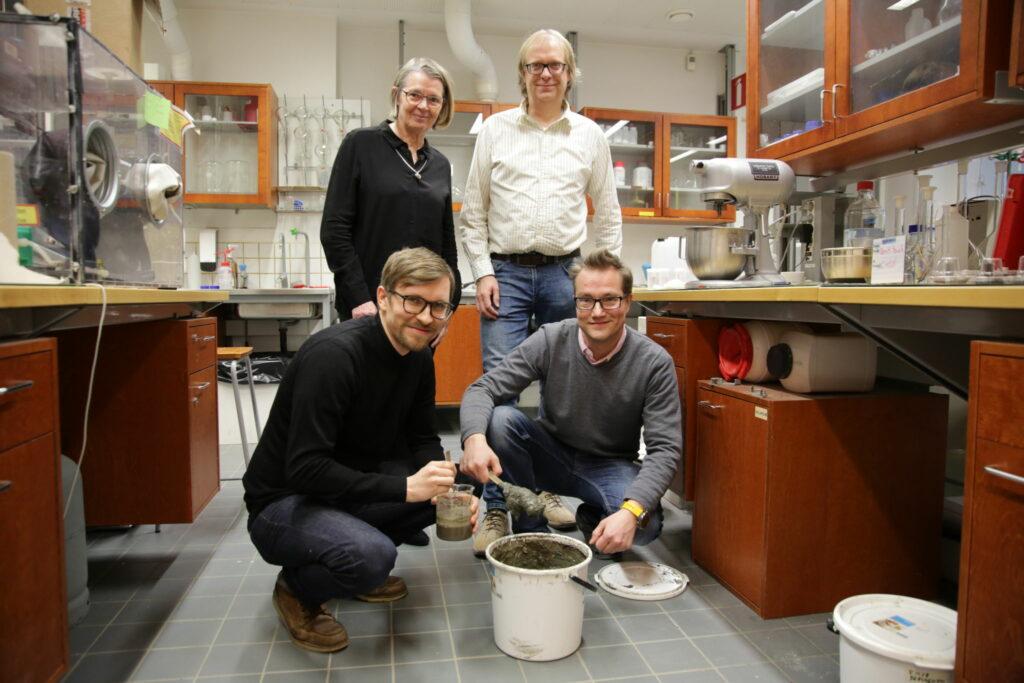Forskargruppen i laboratoriet med en hink lera från Aura å på golvet.