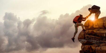 Två klättrare hjälper varandra uppför en klippa.