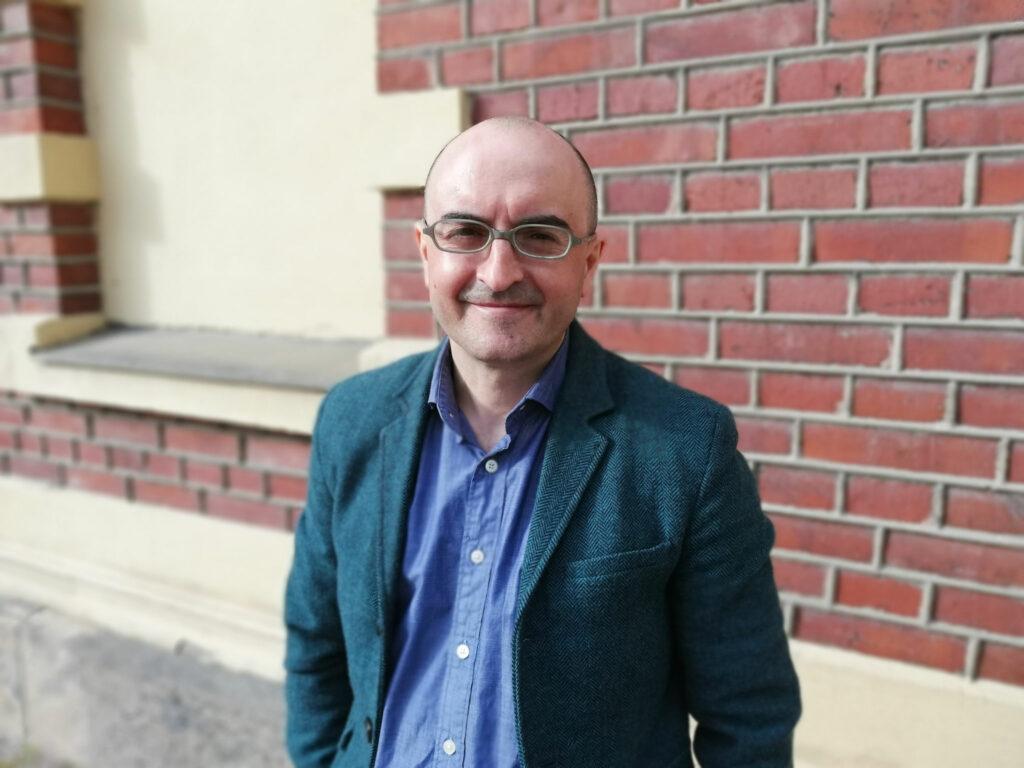 Porträttfoto på Cataldo De Blasio framför en tegelvägg.