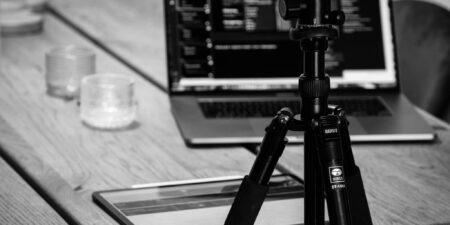 Bild på telefon som är riggad på ett stativ. I bakgrunden syns en laptop på ett bord.