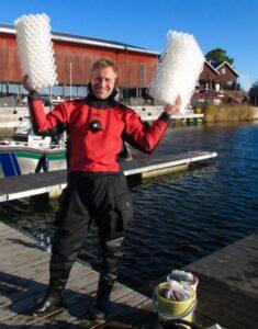 Biträdande professor Christoffer Boström i dykdräkt visar näten som använts i studien.